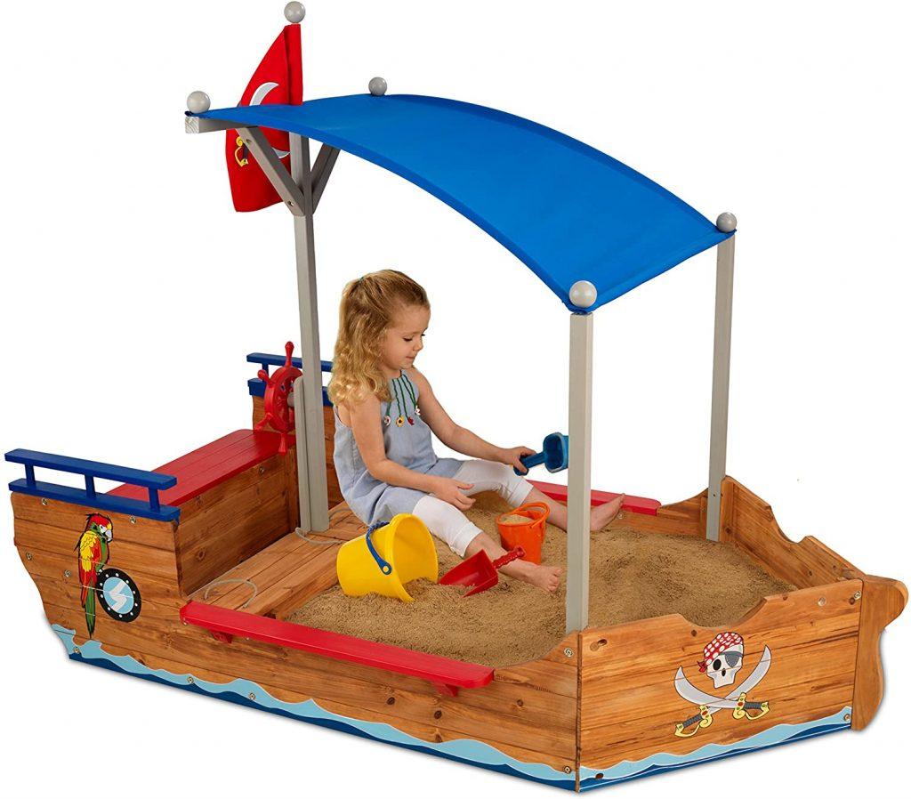 Ce bac à sable en bois Kidkraft a la forme d'un bateau.