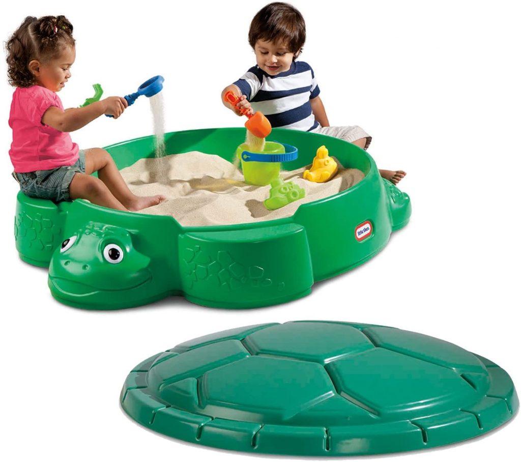 Le bac à sable en plastique avec couvercle Little Tikes est en forme de tortue.